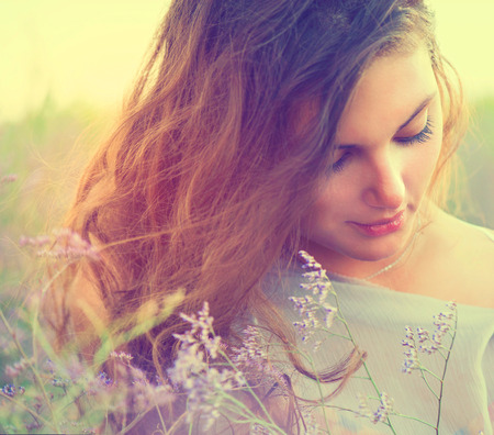 violeta: Mujer sensual que miente en un prado con flores de color violeta Foto de archivo