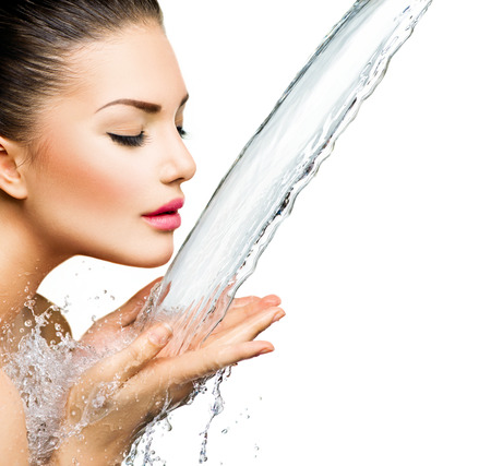 Beautiful smiling girl under splash of water  photo
