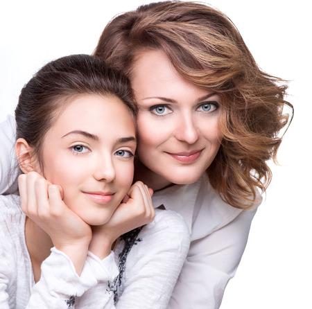 魅力的な幸せな母と笑みを浮かべての十代の娘