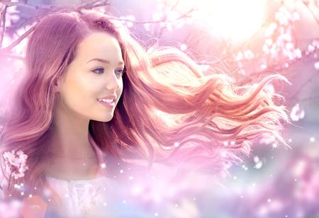 ファンタジー魔法の春の庭で美しい少女 写真素材