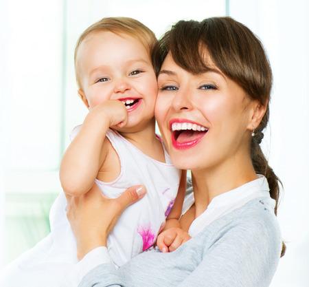 dientes sanos: Madre y bebé besos y abrazos en el hogar Foto de archivo
