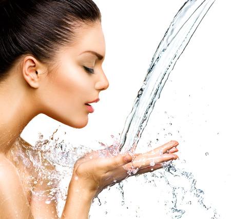 Schöne Frau mit Spritzern von Wasser in den Händen