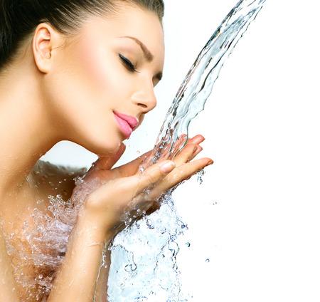 Hermosa muchacha sonriente bajo el chapoteo del agua con la piel fresca Foto de archivo