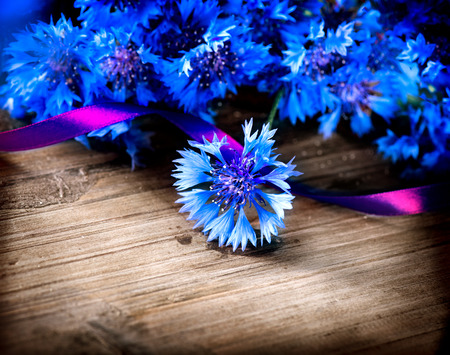 Cornflowers over wooden background  Wild blue flowers photo