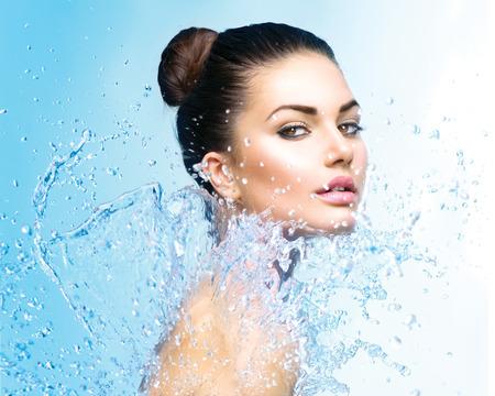 青い背景上の水のしぶきの下で美しい少女
