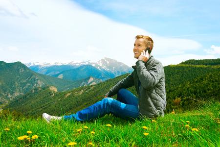 Casual vestindo homem que fala no telemóvel montanhas ao ar livre Imagens