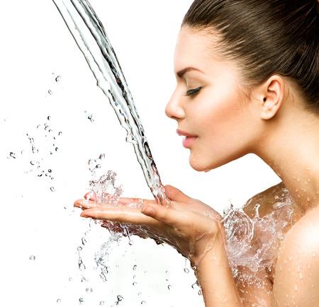 Mulher bonita modelo com salpicos de água em suas mãos