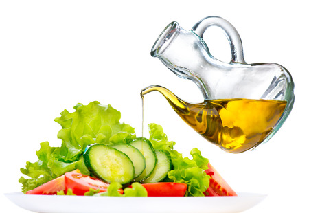 plates: Healthy vegetable salad with olive oil dressing over white Stock Photo