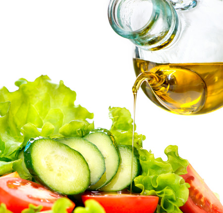 Healthy vegetable salad with olive oil dressing over white Stock Photo