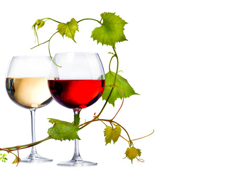 Two glasses of red and white wine decorated with grape leaves Stock Photo