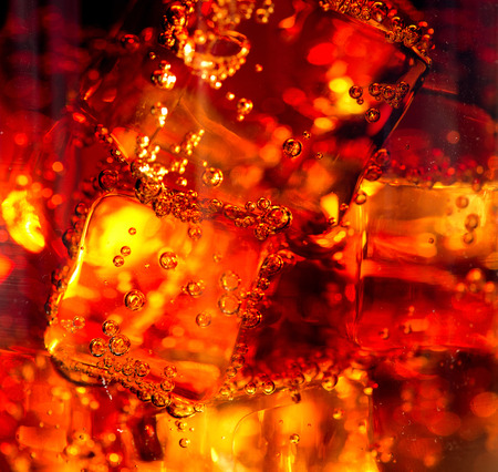 Cola with ice and bubbles in glass closeup photo