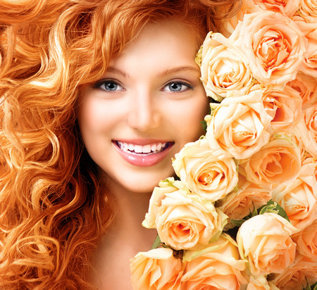Girl with long curly red hair and beautiful roses