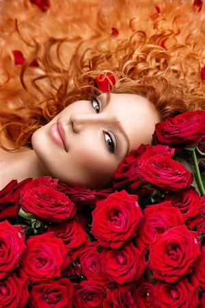 mazzo di fiori: Donna con capelli rossi permanentati e belle rose rosse