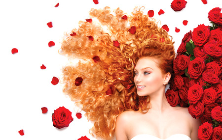 Beauty model girl with curly red hair and beautiful red roses photo