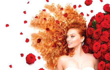 rosas rojas: Chica modelo de la belleza con el pelo rojo rizado y hermosas rosas rojas Foto de archivo