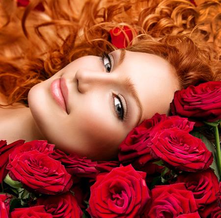 Mujer con el pelo rojo con permanente y hermosas rosas rojas Foto de archivo