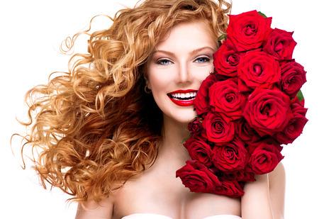 Donna di bellezza con lunghi capelli rossi permanentati e belle rose rosse Archivio Fotografico - 29053670