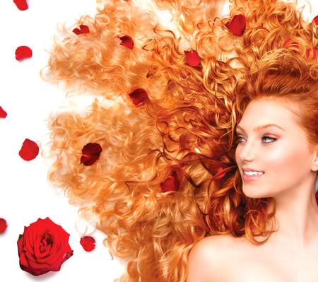 Muchacha de la belleza con el pelo largo rizado de color rojo y hermosas rosas rojas Foto de archivo