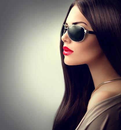 Model van de schoonheid meisje met lang bruin haar dragen van een zonnebril Stockfoto