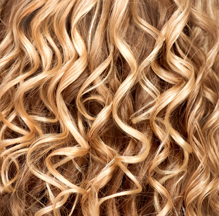 Wavy curly blonde hair closeup  Texture of permed hair Stock Photo