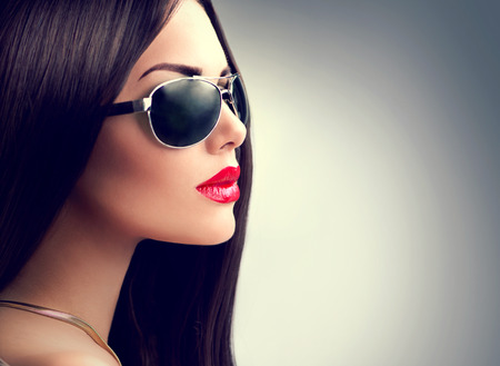 Beauty model girl with long brown hair wearing sunglasses photo