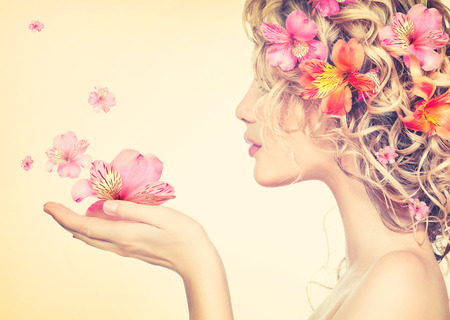 Girl takes beautiful flowers in her hands  Blowing flower photo