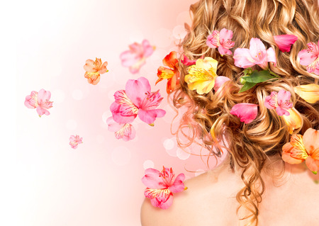 Beautiful healthy curly hair decorated with flowers photo