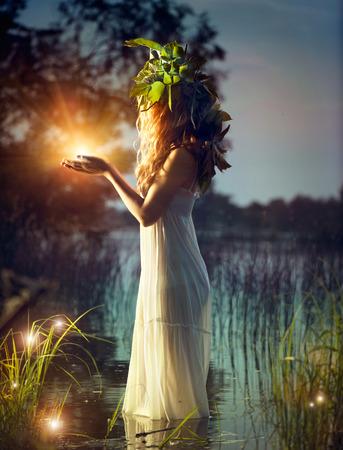 魔法の光神秘的な夜のシーンを取っているファンタジー女の子