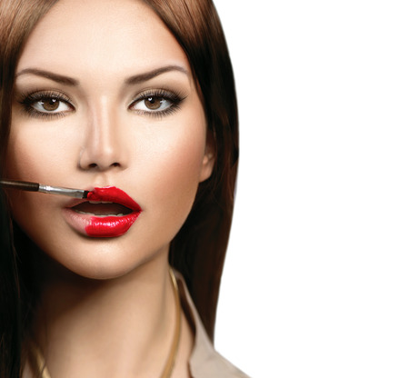 Beauty fashion model girl applying red lipgloss photo