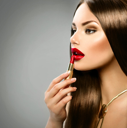 Sexy girl applying makeup  Red lipstick photo