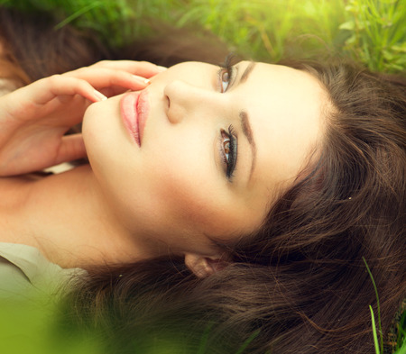 Beauty woman lying on the field and dreaming  Enjoying nature Imagens