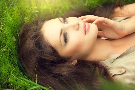 Belleza de la mujer tendido en el terreno y soñando Disfrutar de la naturaleza