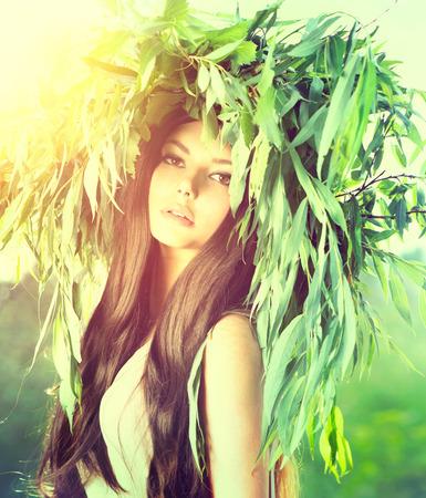緑の花輪の長い茶色の髪と美しさのモデルの女性