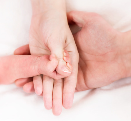 Hands of mother, father and newborn baby photo