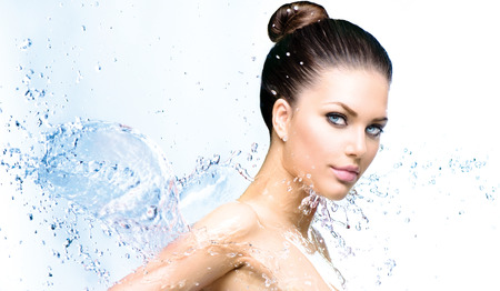 Beautiful smiling girl under splash of water with fresh skin photo