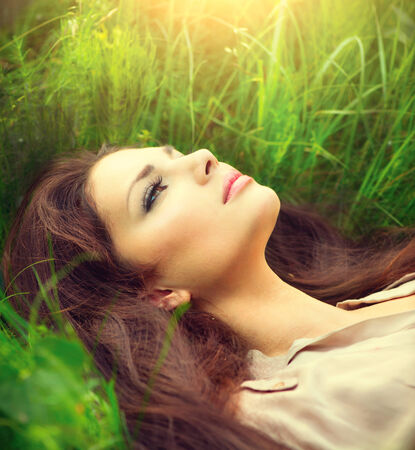 Beauty woman lying on the field and dreaming  Enjoying nature photo