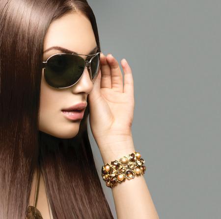 Chica modelo de la belleza con el pelo largo y castaño con gafas de sol