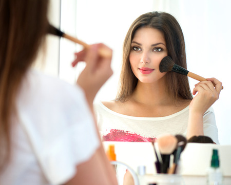 makeup a brush: Beautiful girl looking in the mirror and applying makeup