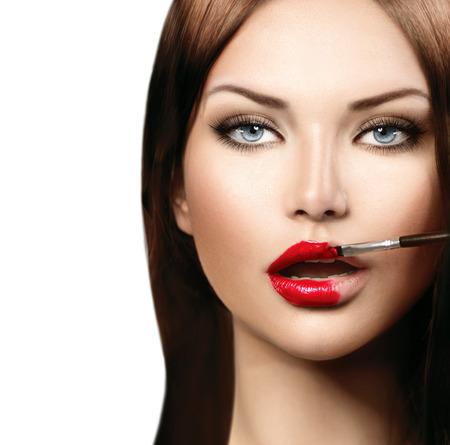 Bellezza modella ragazza applicando lipgloss rosso