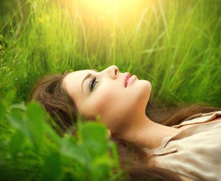 美女: 美麗的女人躺在領域和夢想享受大自然