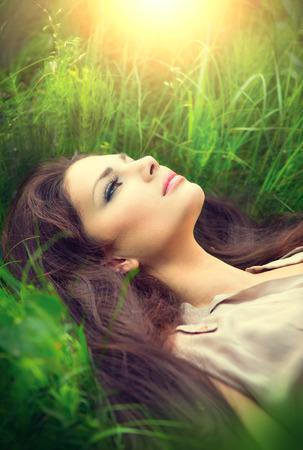 deitado: Mulher da beleza deitado no campo e sonhando Apreciando a natureza Imagens