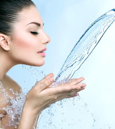 Mooi glimlachend model meisje onder scheutje water over de blauwe Stockfoto