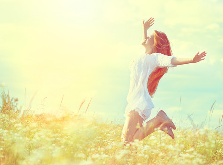 leaping: Beauty model girl in white dress jumping on summer field Stock Photo