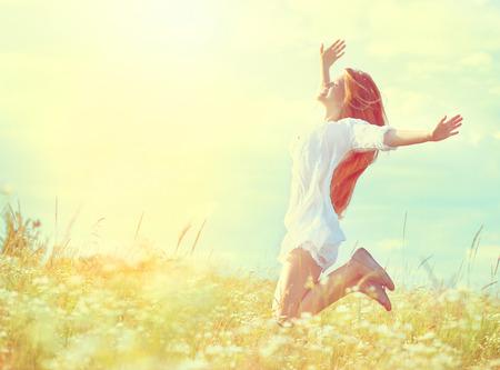 Chica modelo de la belleza en vestido blanco saltando en el campo de verano
