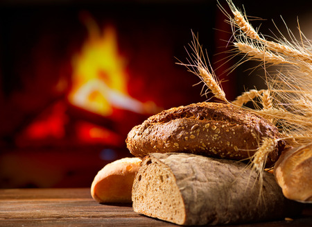 Various Bread and Sheaf of Wheat Ears on a Wooden Table photo