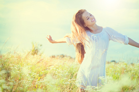 Beauty model girl in white dress having fun on summer field photo