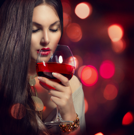 Beauty Young sexy woman drinking red wine over night background photo