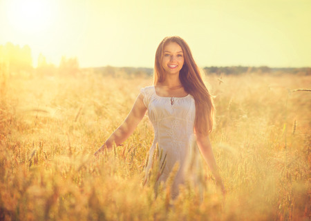 Beautiful teenage model girl in white dress running on the field photo