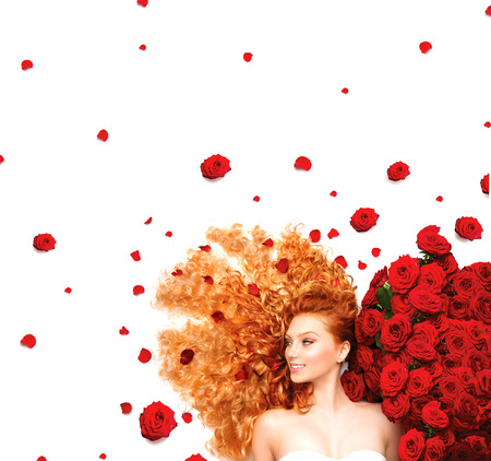 Beauty model girl with long curly red hair and red roses