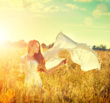 Beauty girl in white dress on summer field enjoying nature photo